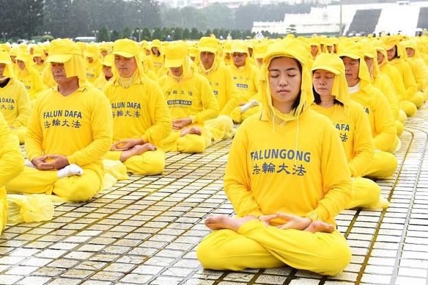 約6400名來自台灣及世界各地部分法輪功學員,11月25日齊聚在中正紀念堂排字,雖然台北雨勢不斷,但他們風雨無阻。圖為法輪功學員演煉功法。(孫湘詒/新唐人)